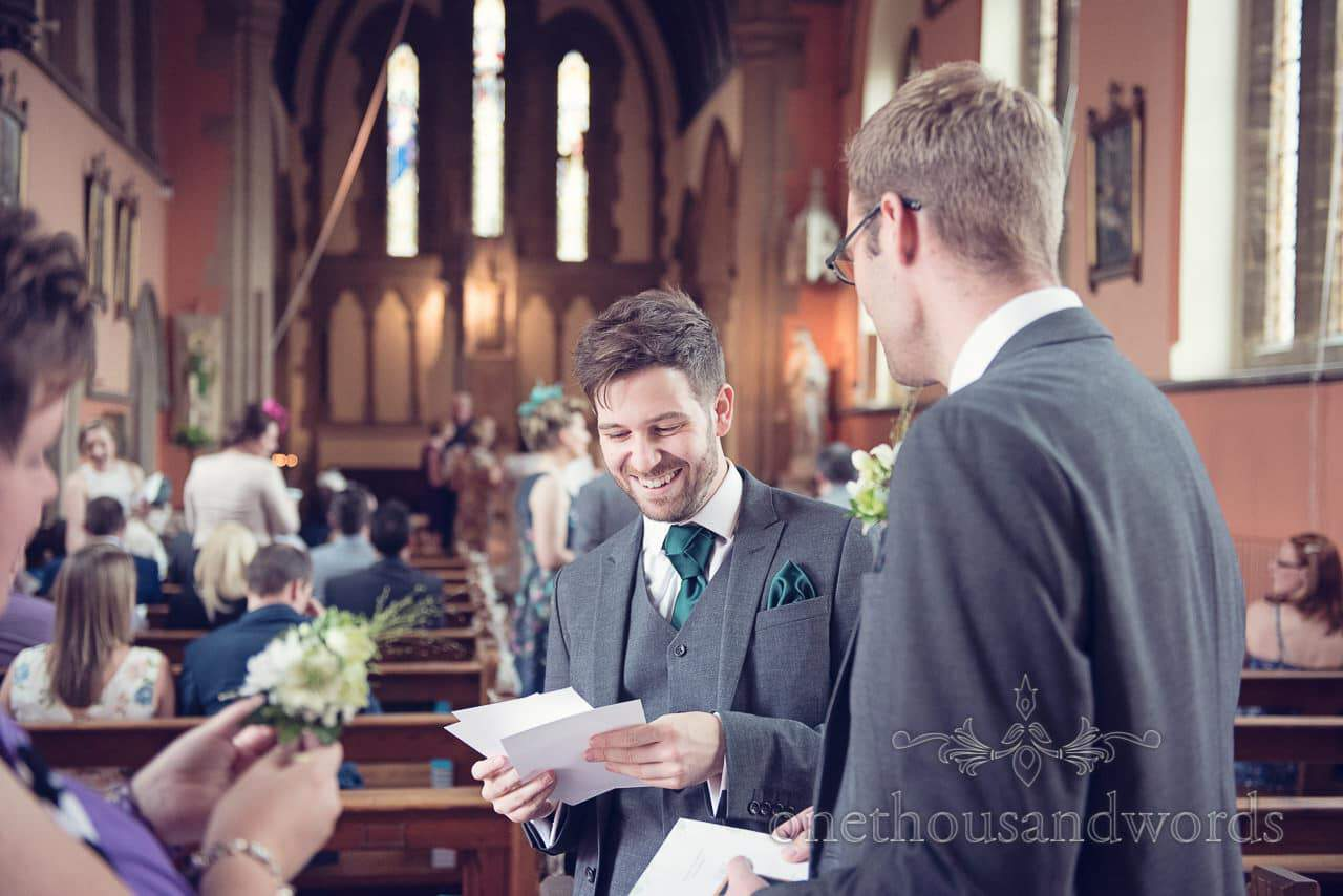 Groom in green weddign tie with trinity knot welcomes wedding guests to church