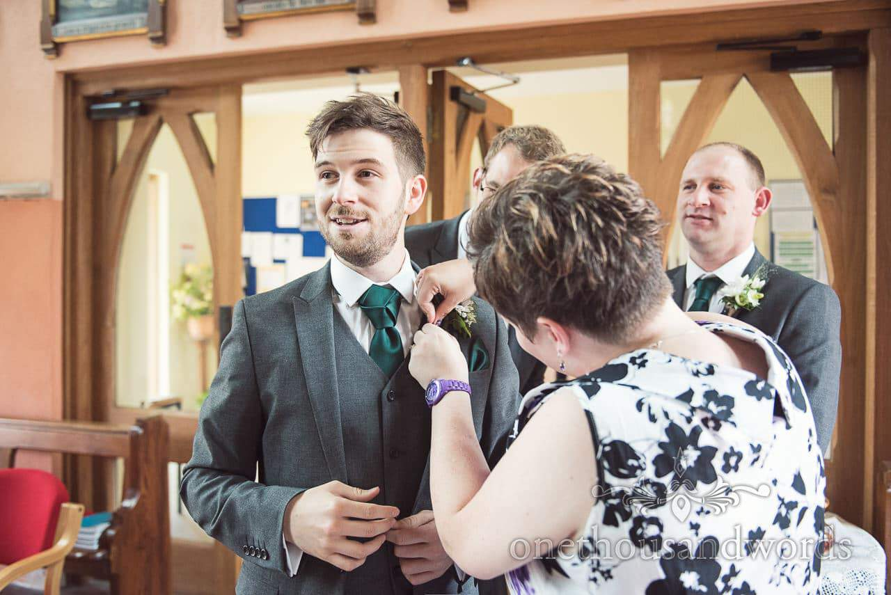Groom in green wedding tie has button hole adjusted in church