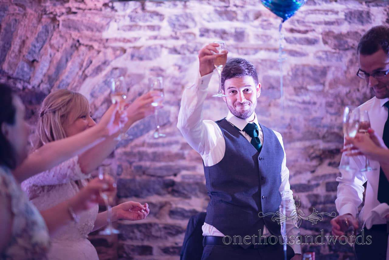 Groom in grey waist coat makes wedding toast at Barn wedding venue