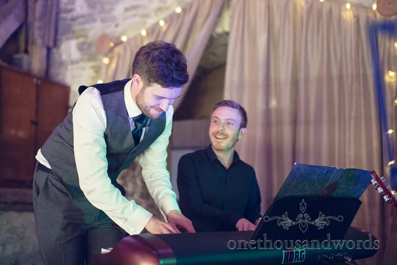 Groom in grey waistcoat plays keyboard at barn wedding venue in Dorset