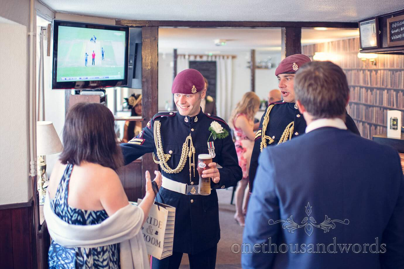 Groom in military uniform drinks a beer and greets guests at pub