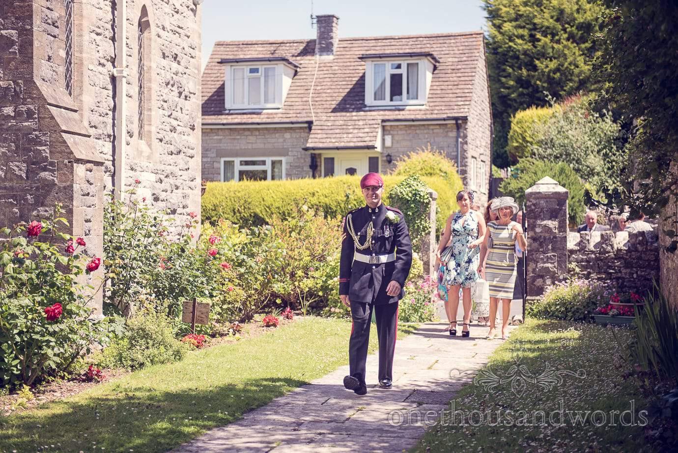 Groom in military uniform walks into church wedding garden in Swanage