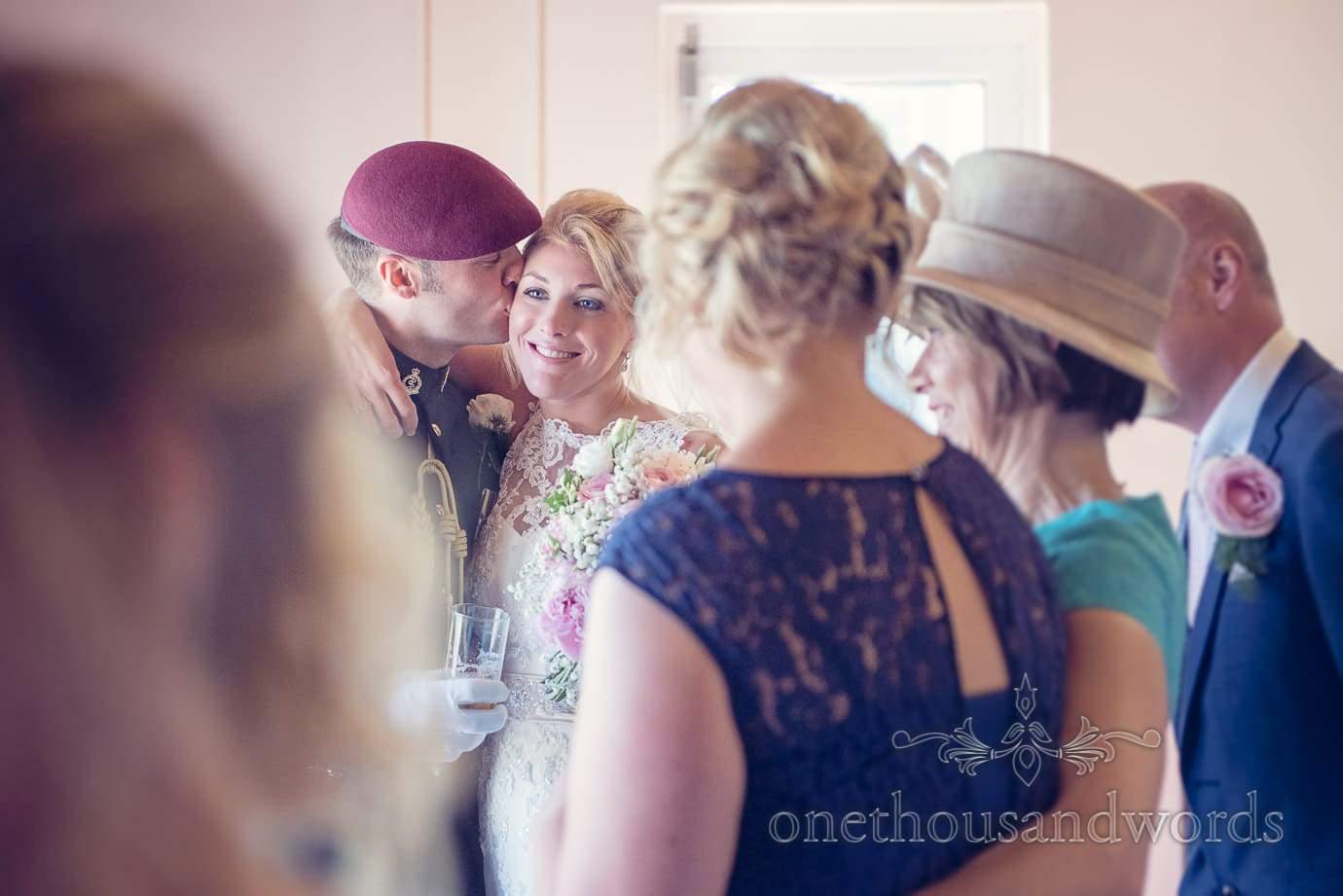 Groom kisses bride as wedding party waits for wedding breakfast
