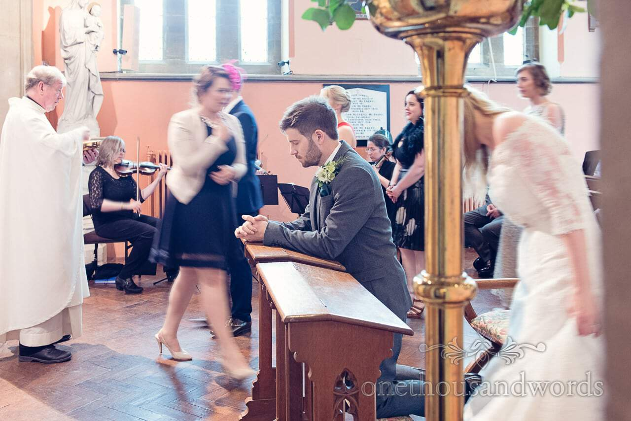 Groom prays in Catholic church wedding ceremony during communion