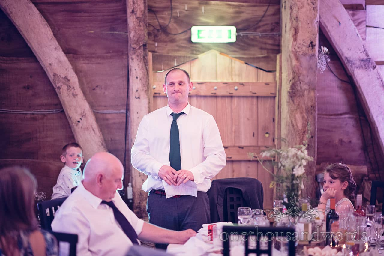 Groom's brother delivers his best man's speech at wooden barn wedding venue