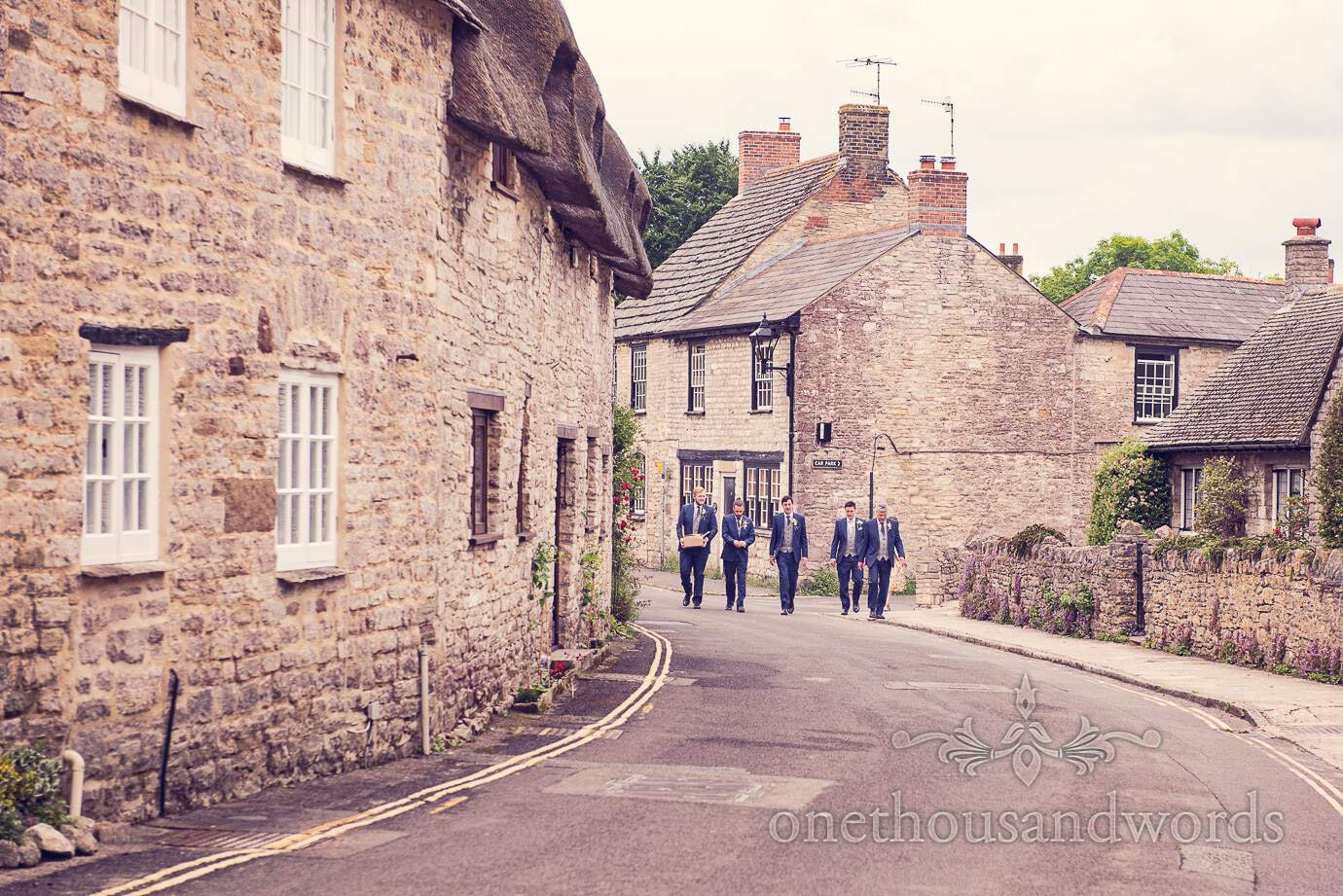 Groomsmen in blue wedding suits walk through Dorset countryside village