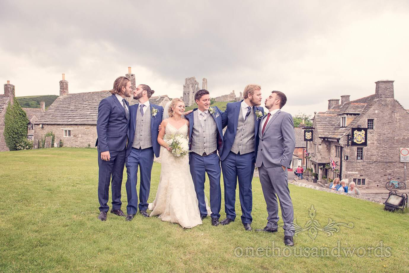 Groomsmen kiss during group photographs at Corfe Castle wedding