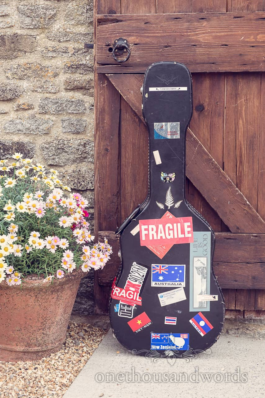 Guitar case with stickers leans on wooden door at Dorset Barn Wedding