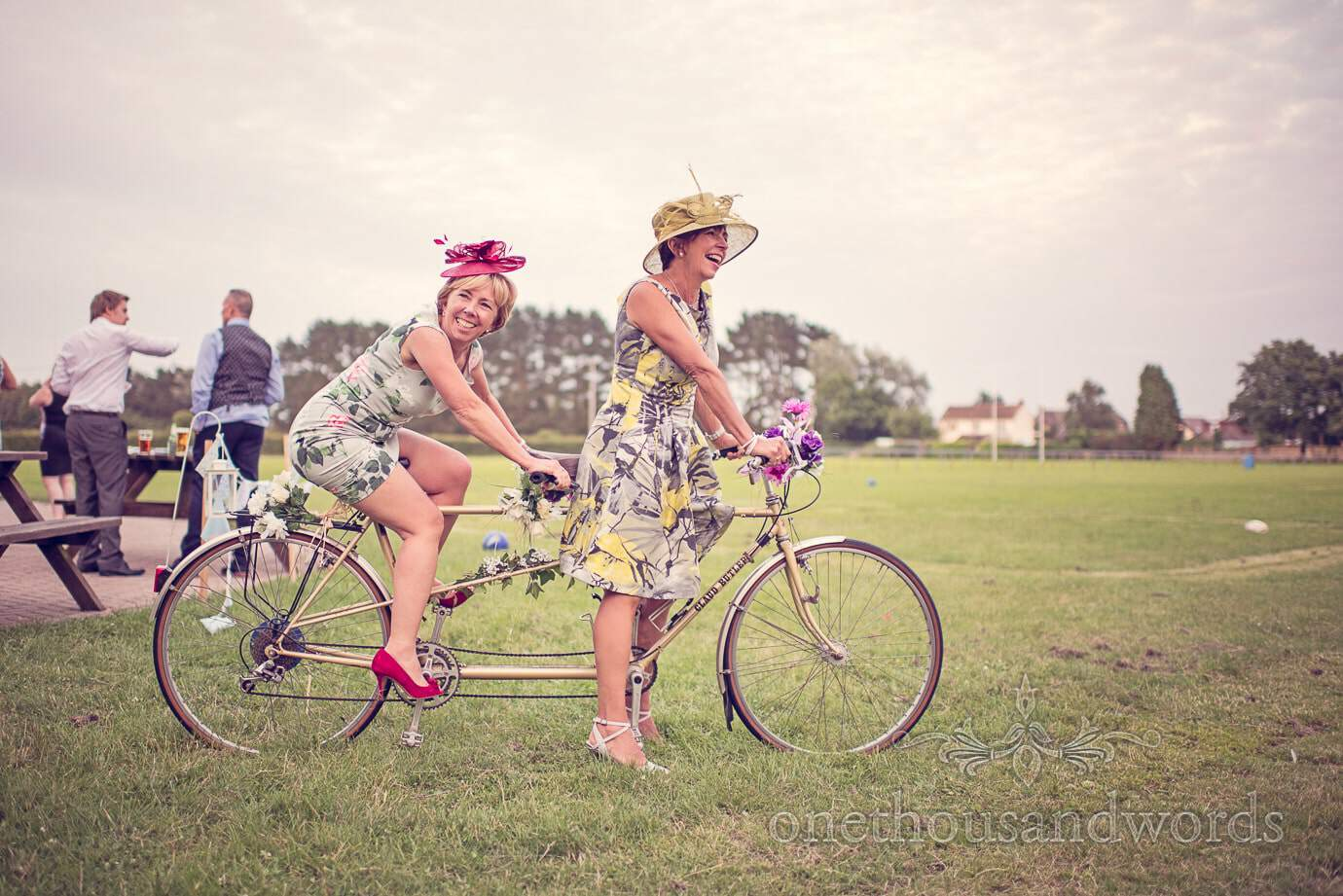 Happy wedding guests ride tandem wedding bike at Wareham Rugby Club