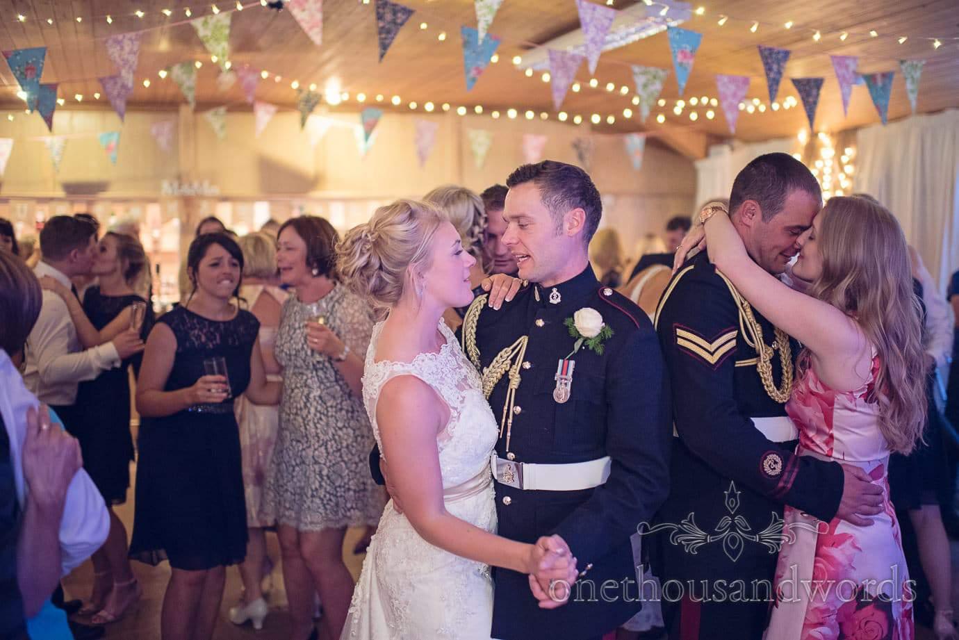 Military wedding dancing in uniform under bunting at Wareham Rugby Club wedding