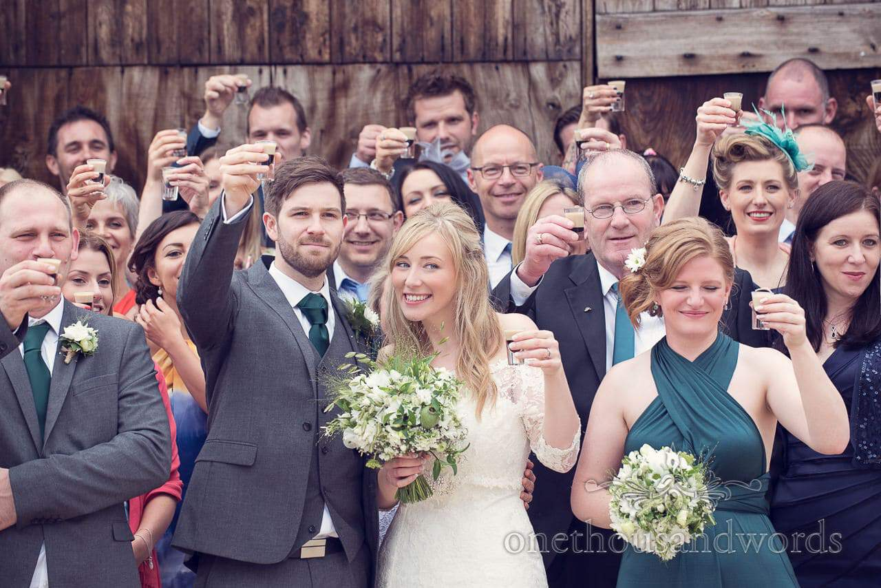 Mini Guinness toast during group wedding photographs at barn wedding