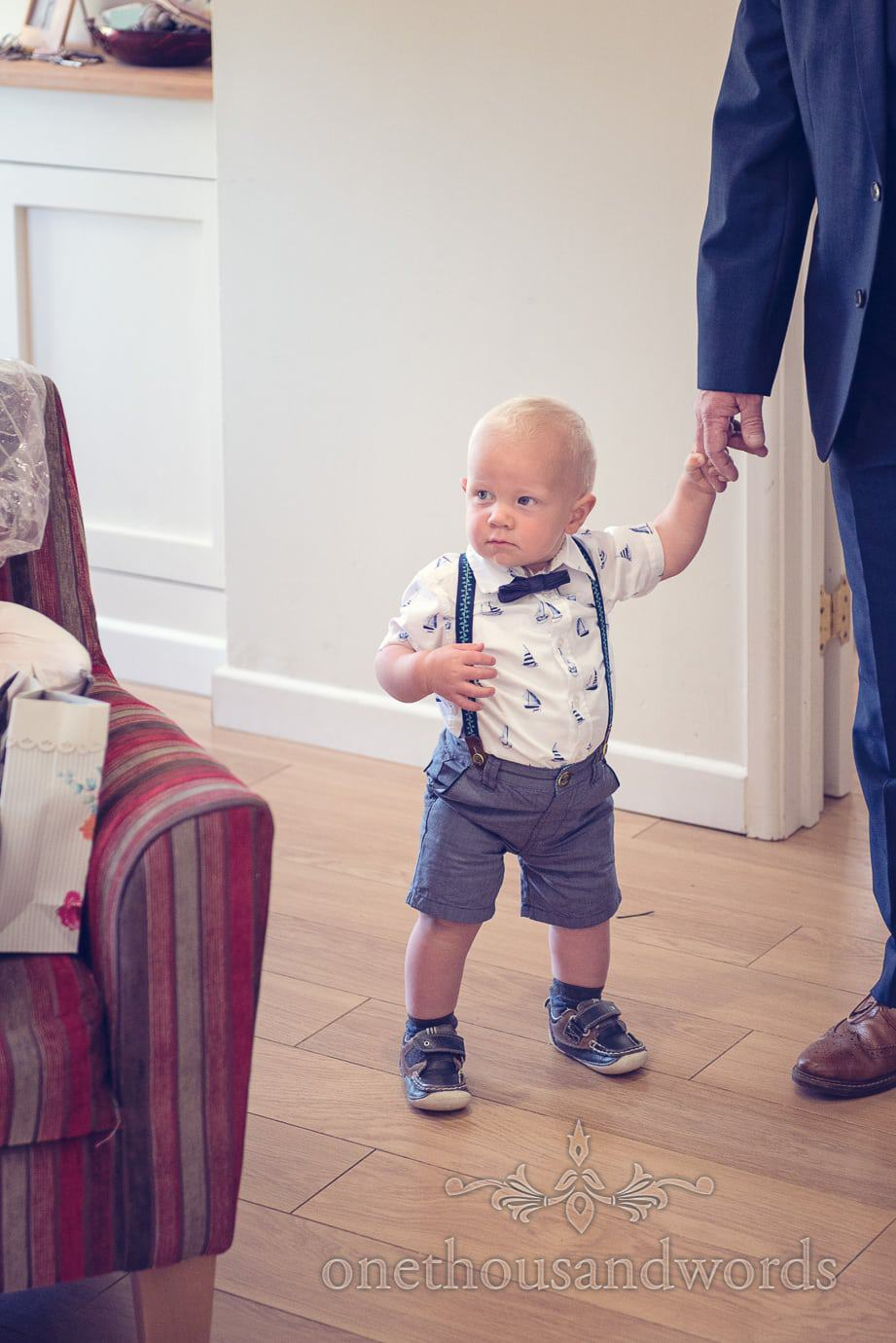 Pageboy baby in bow tie and braces on wedding morning in Dorset