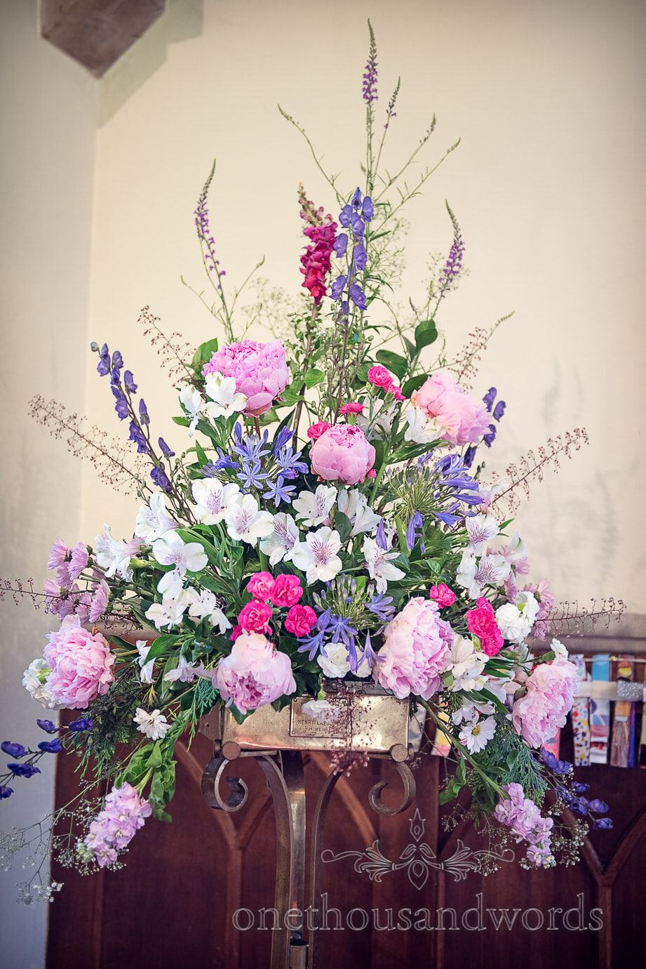 Pastel wedding flowers dispay in church by Wildberry Flowers, Dorset