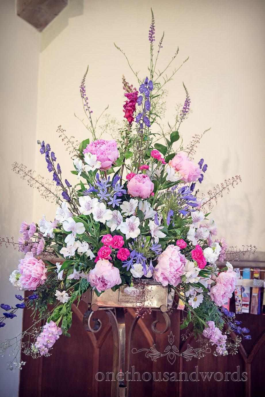 Pastel wedding flowers dispay in church by Wildberry Flowers, Dorset