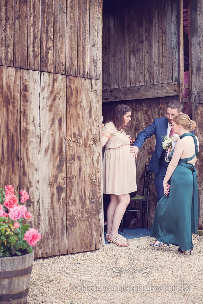 Pregnant wedding guest with huge wooden doors at Dorset barn wedding venue