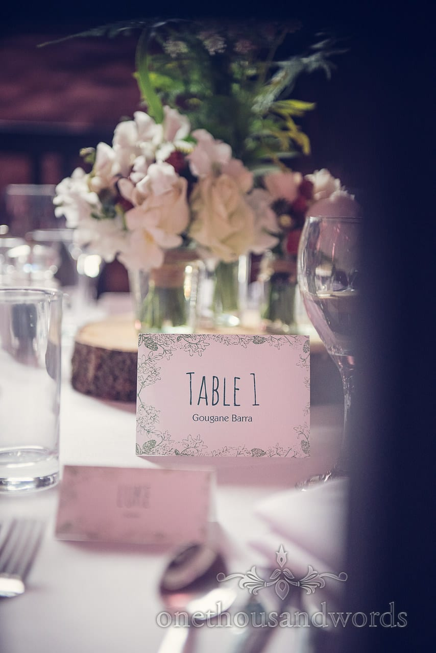Table place name with white wedding flowers at Dorset Barn wedding