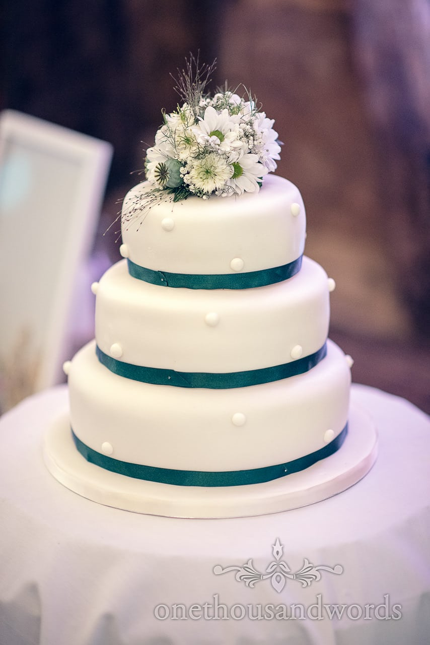 Three tier white wedding cake with green ribbon and white and green flowers