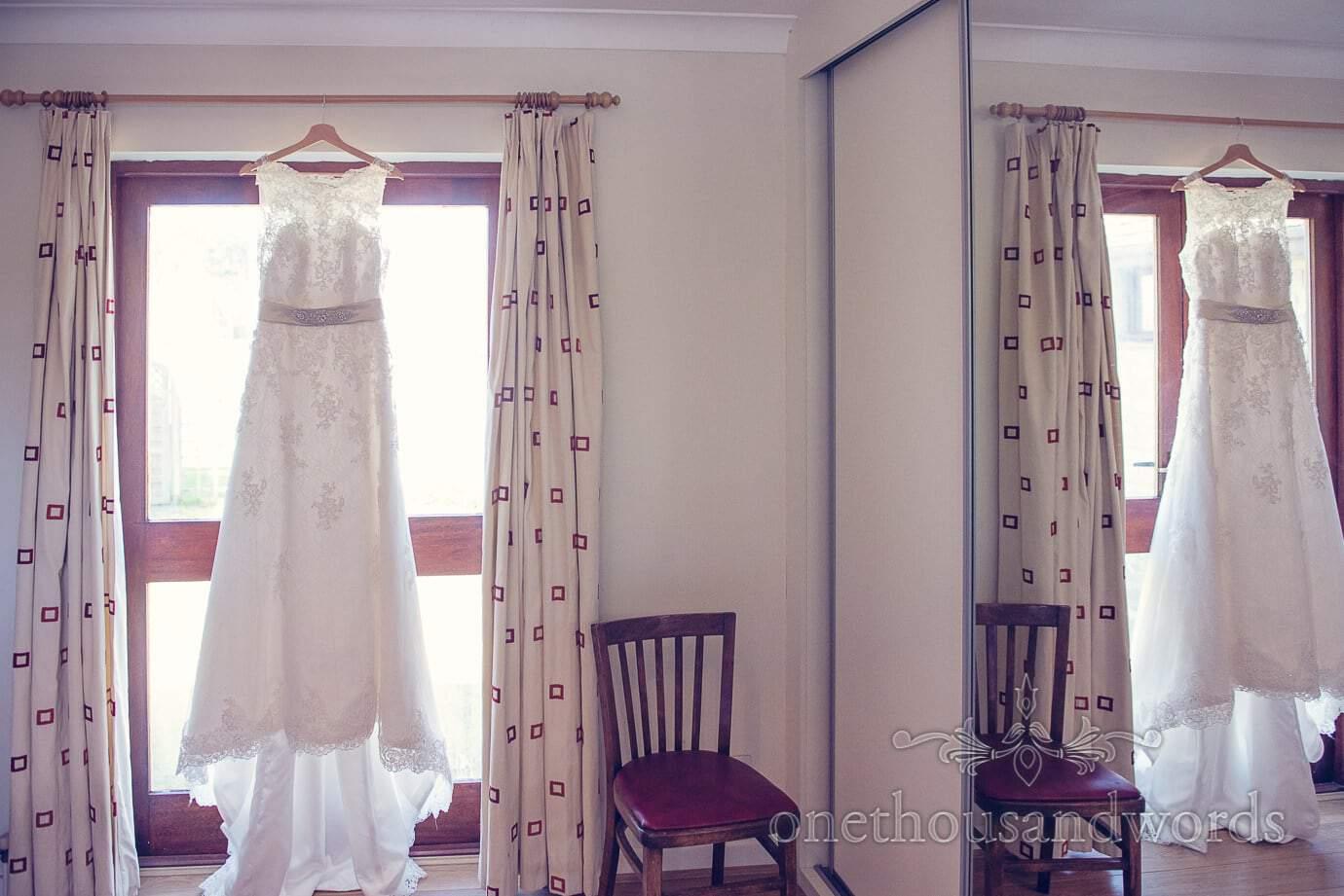 Wedding dress hangs in bedroom window and mirror on wedding morning
