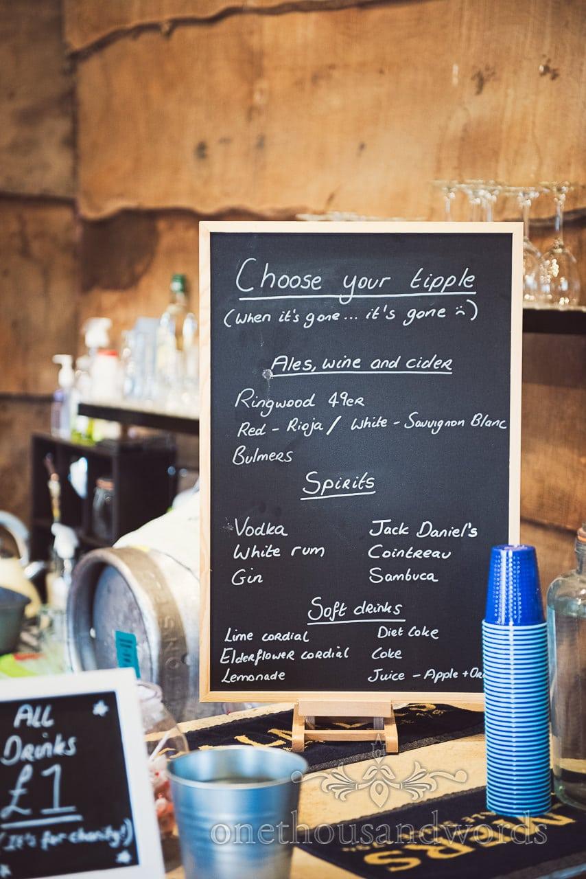 Wedding drinks menu on chalk blackboard in wooden barn venue