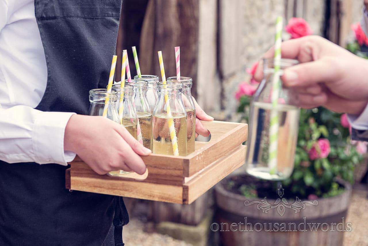 Wedding drinks reception prosecco in retro milk bottles with candy stripe straws