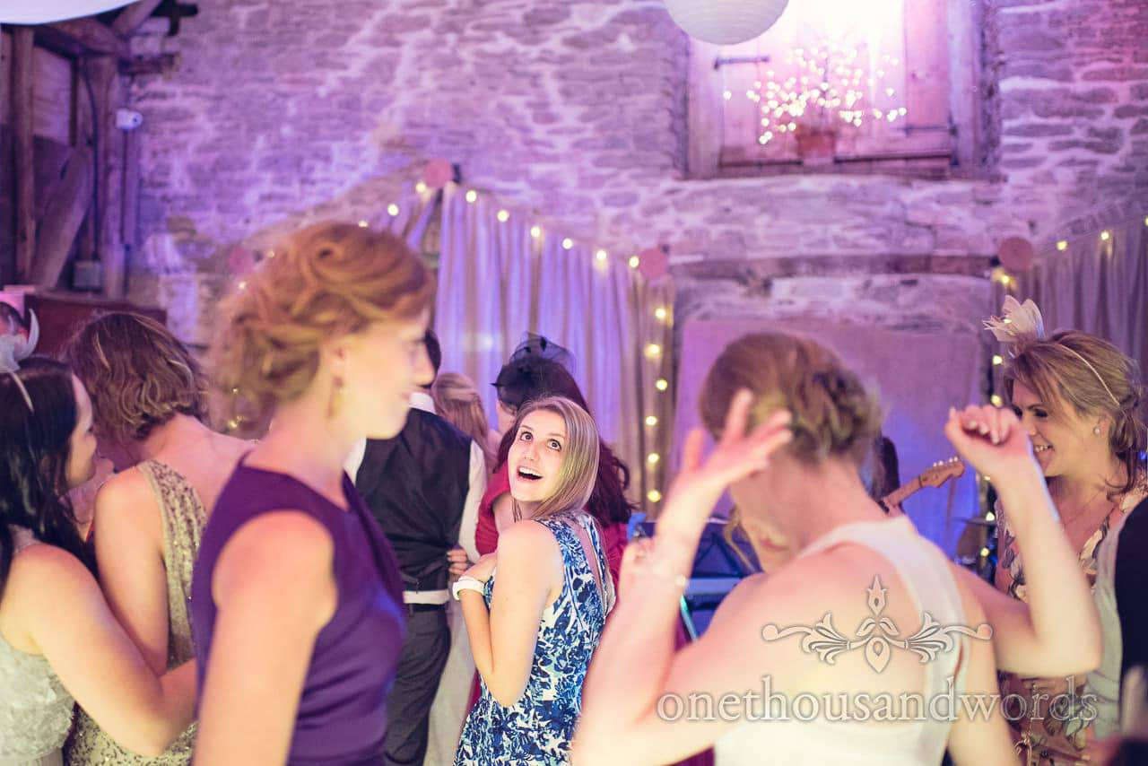 Wedding guest dances infront of fairy lights at Barn Wedding Venue