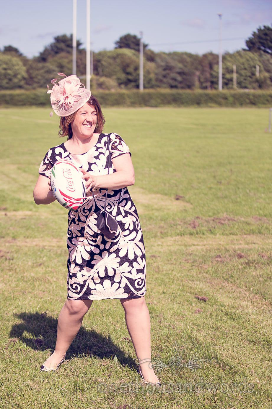 Wedding guest in black and white dress plays rugby at drinks reception