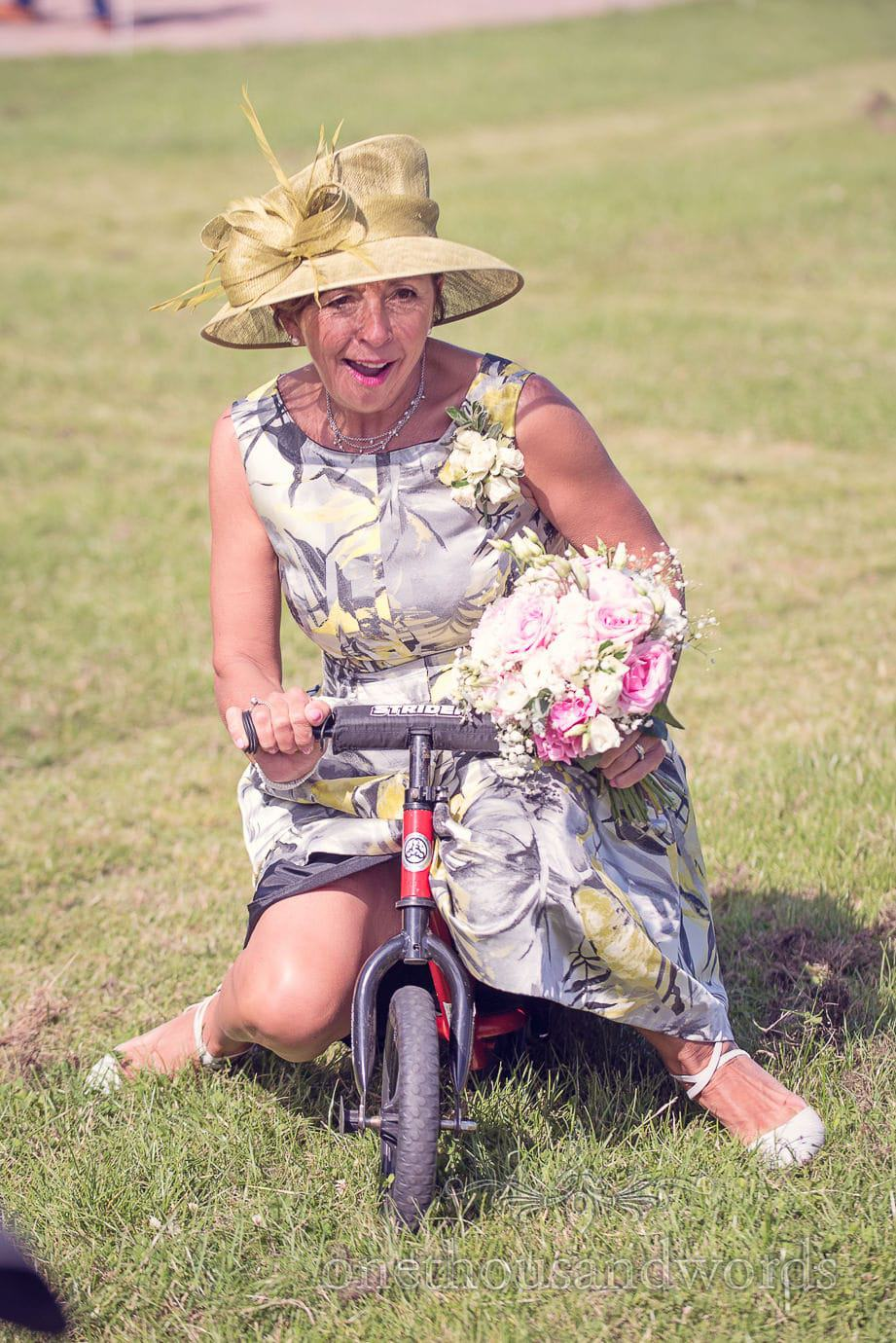 Wedding guest in stylish dress and hat rides a child's bike