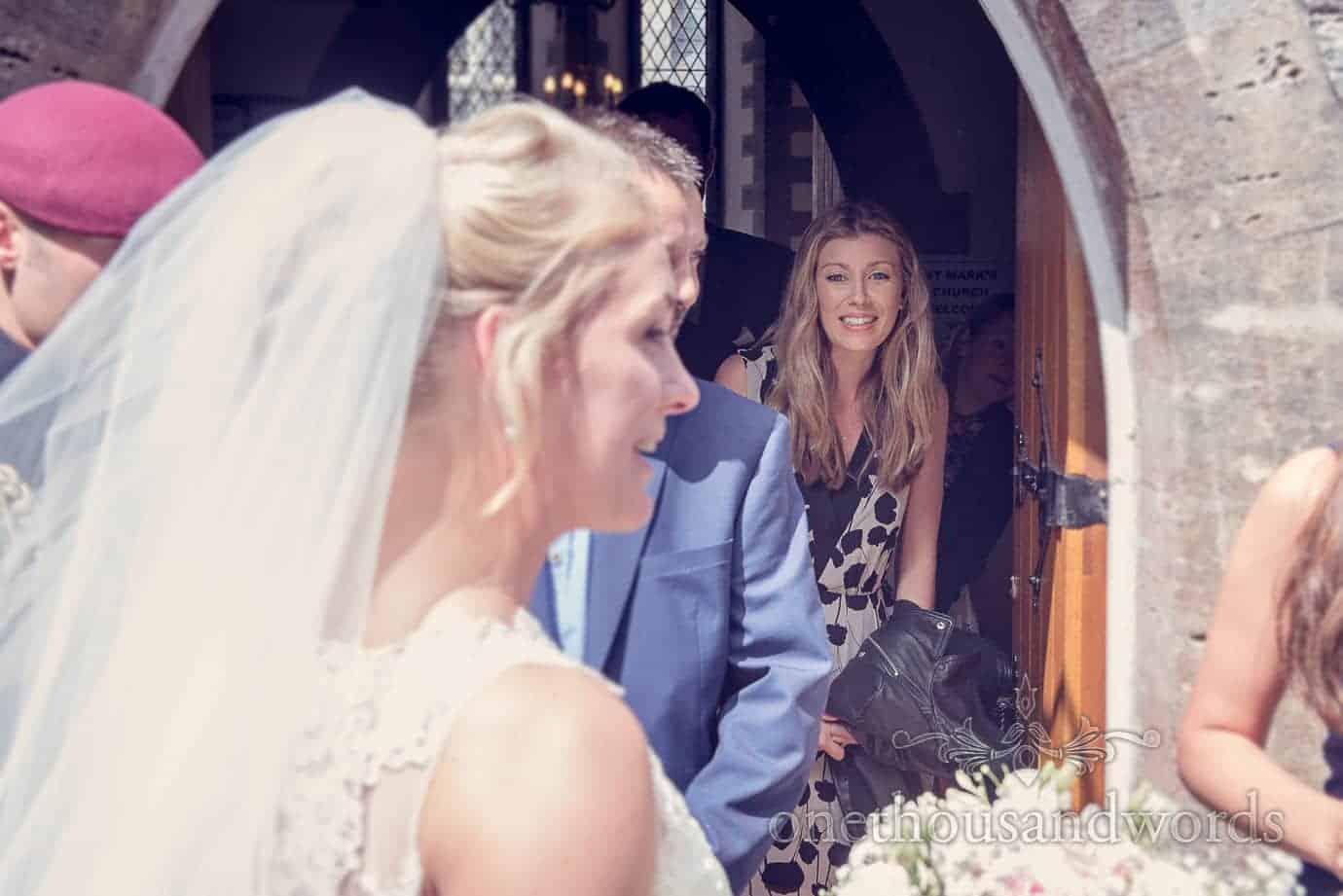 Wedding guest looks through church stone doorway at bride