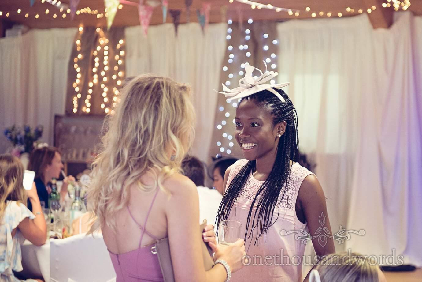 Wedding guest portrait in pink dress and fascinator under fairy lights