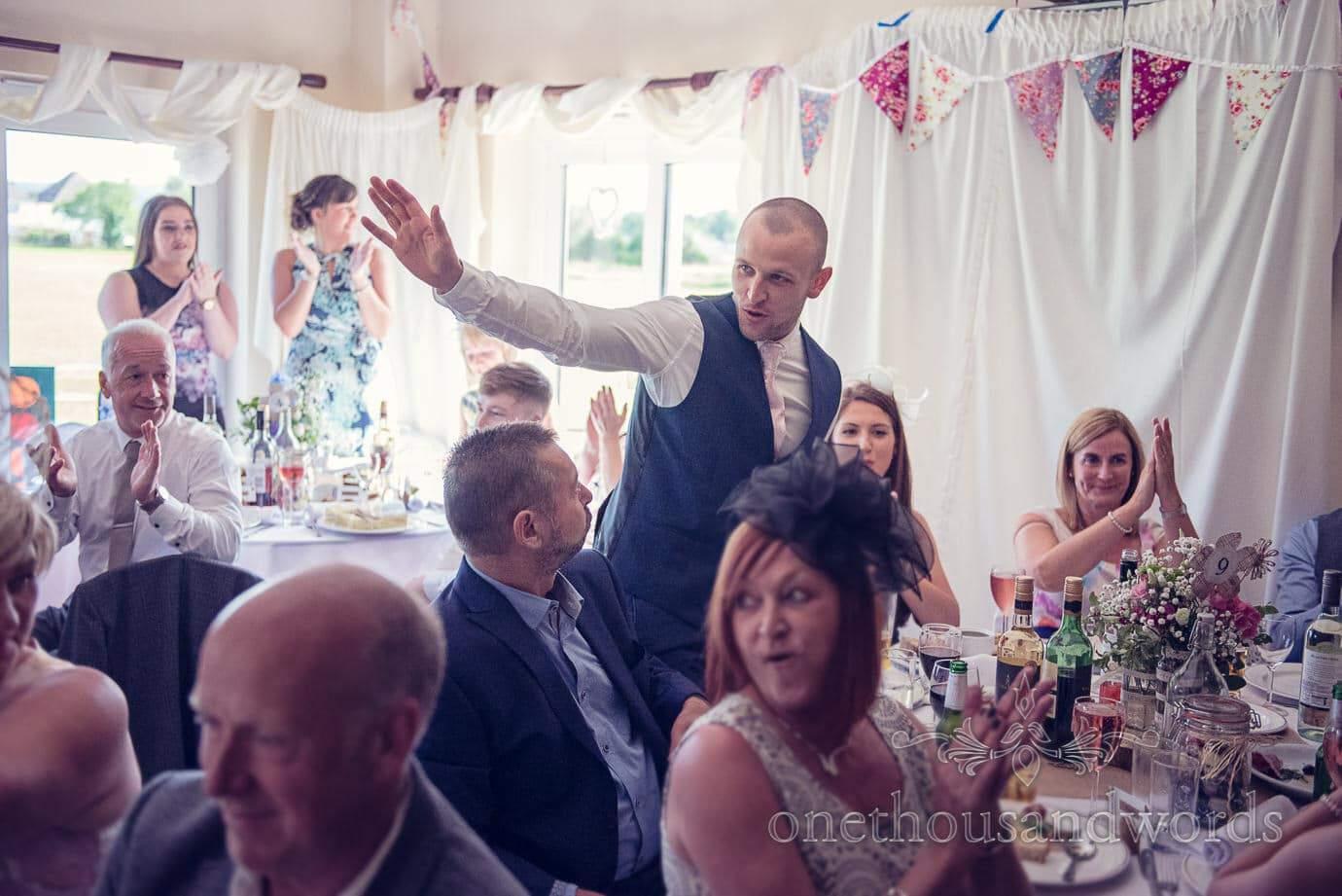 Wedding guest stands for applaudse during wedding speeches