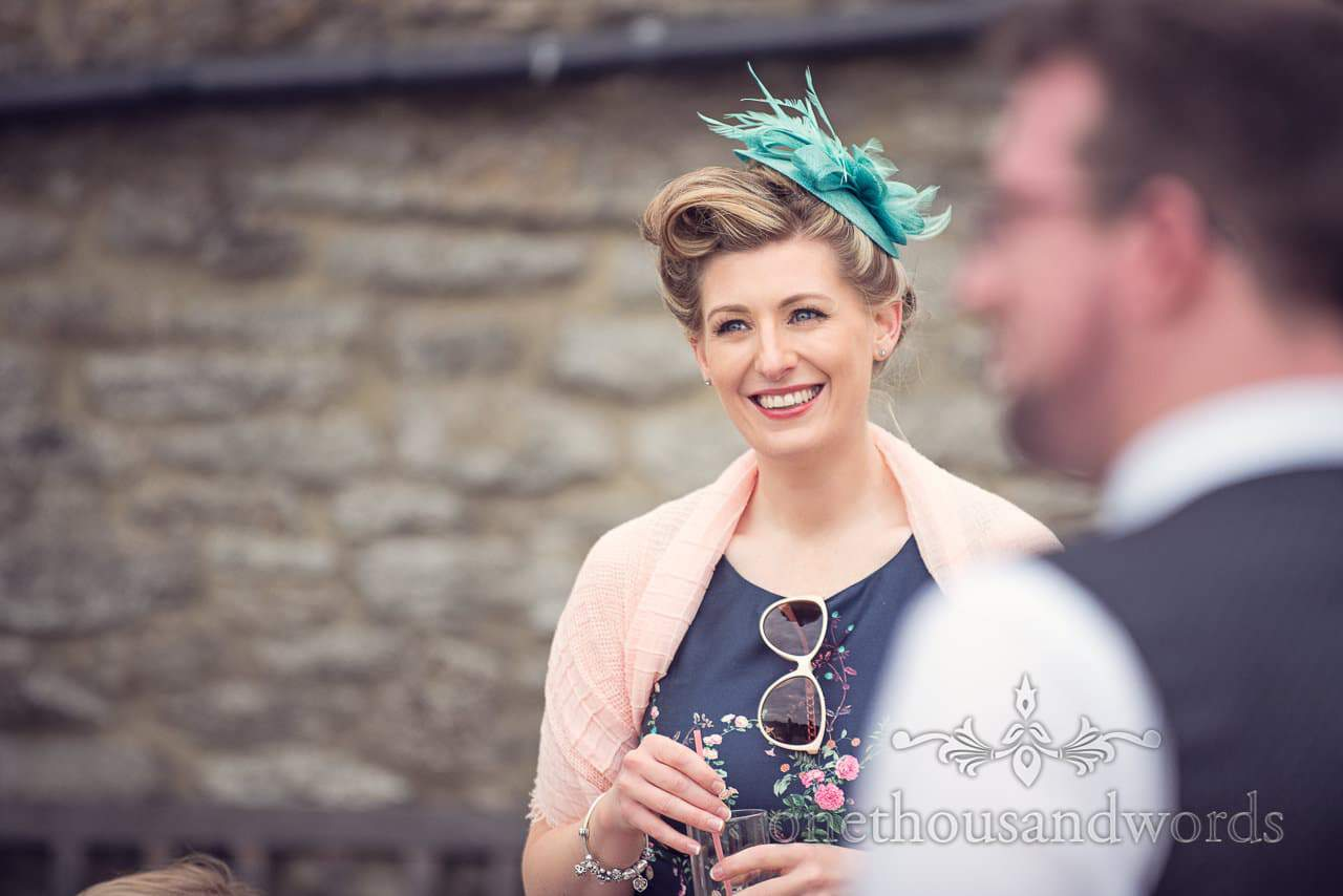 Wedding guest with turquoise fascinator at Dorset Barn wedding venue