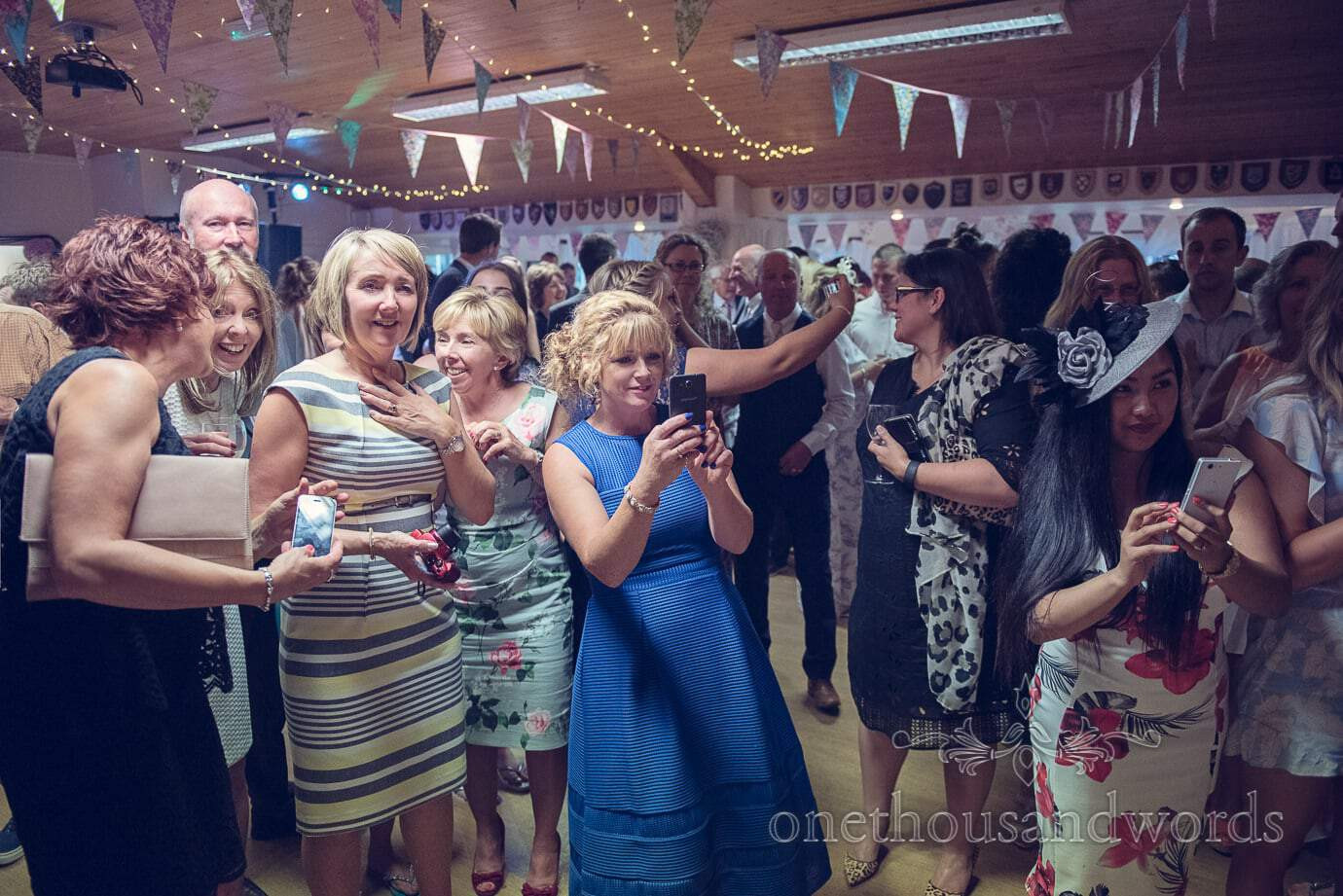 Wedding guests at Wareham Rugby Club Wedding take photographs of bride and groom