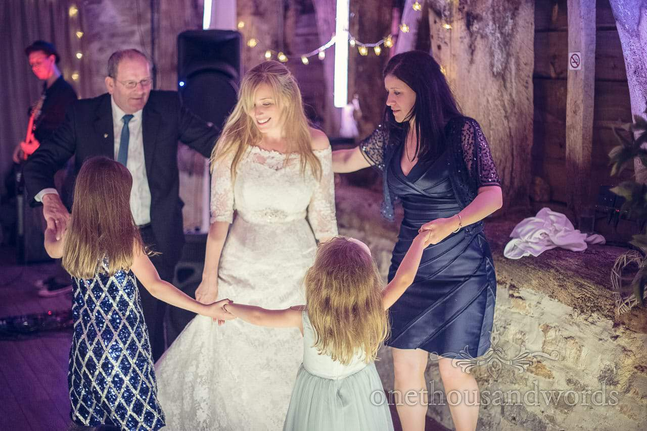 Wedding guests dance in a circle around the bride at barn wedding venue