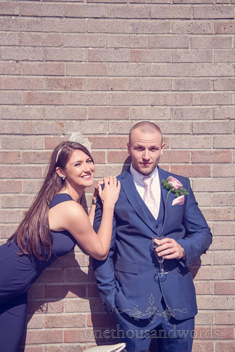 Wedding guests in blue against brick wall at Wareham Rugby Club wedding