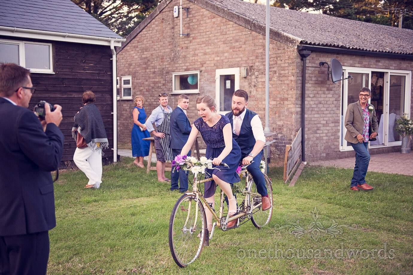 Wedding guests in blue ride tandem bike at Wareham Rugby Club Wedding
