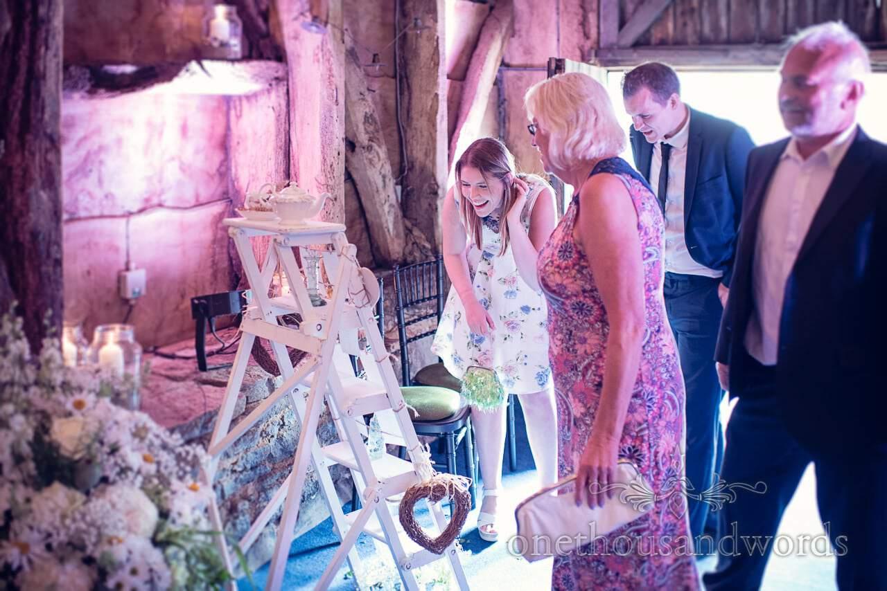 Wedding guests look at table plan at Stockbridge Farm Barn wedding venue in Dorset