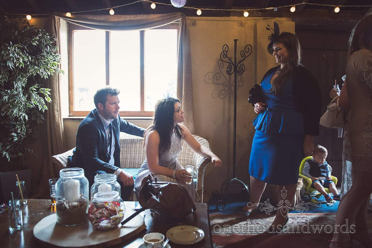 Wedding guests relax in bar area at barn wedding venue in Dorset