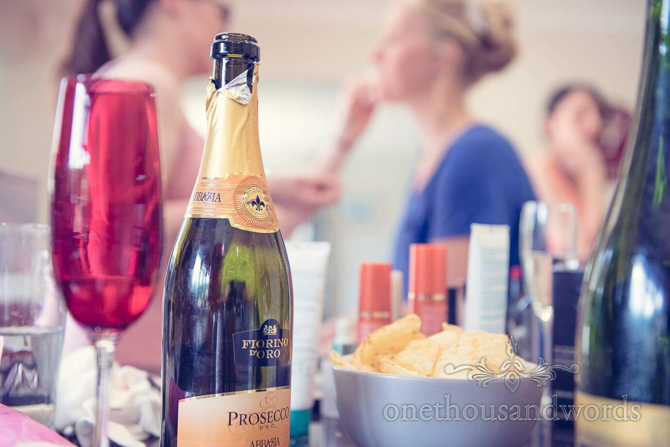 Wedding morning Prosecco with wedding makeup in background