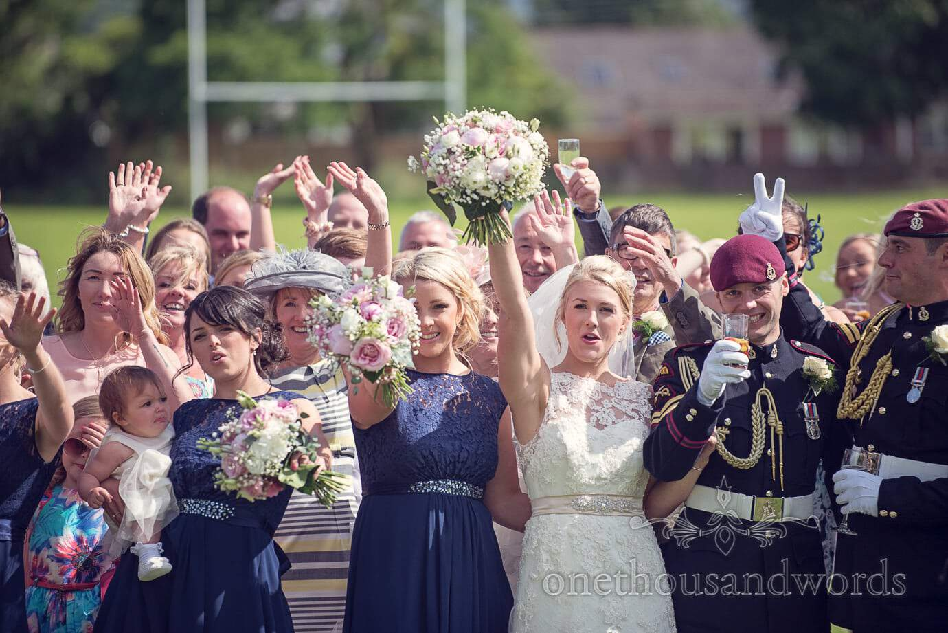 Wedding party cheer and wave during wedding group photographs