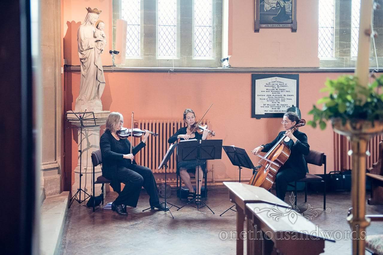 Wedding strings trio play music in church wedding ceremony