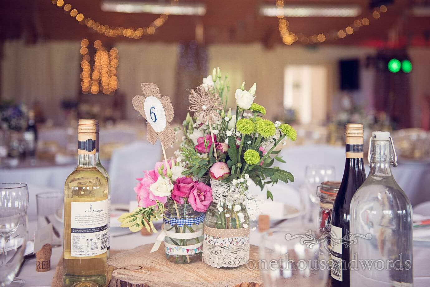 Wedding table floral centerpiece with ribboned jars and country flowers