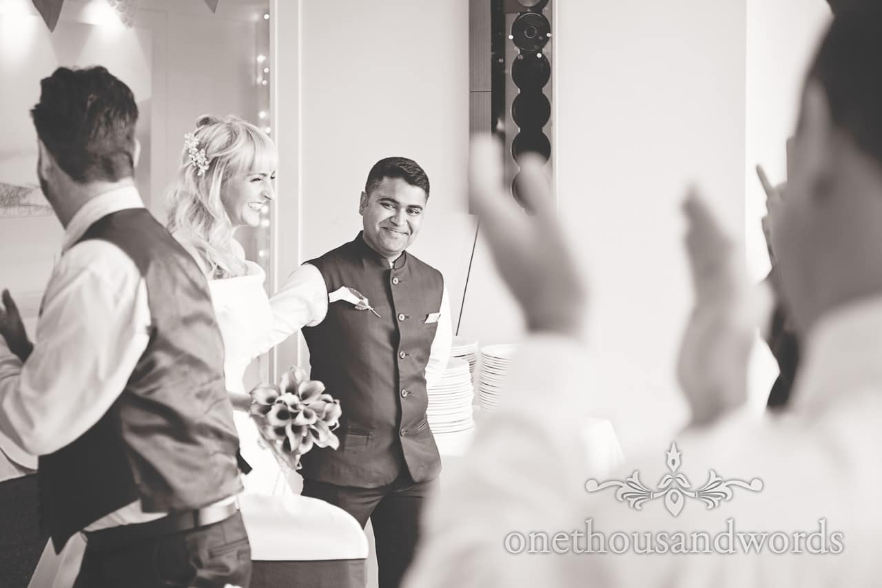 Black and white wedding photograph of bride and groom entering wedding breakfast