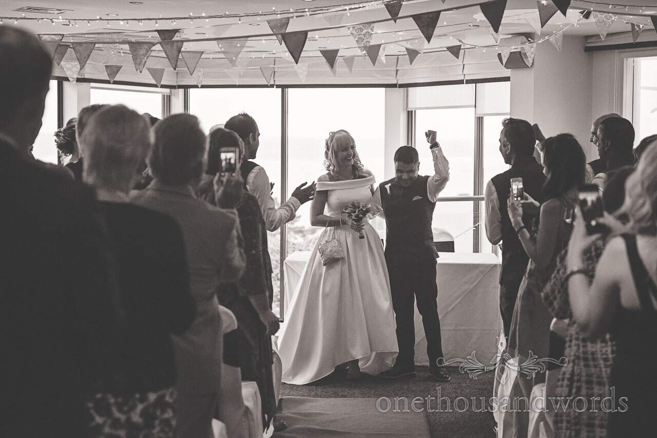 Black and white wedding photograph of groom fist pumping air after wedding ceremony