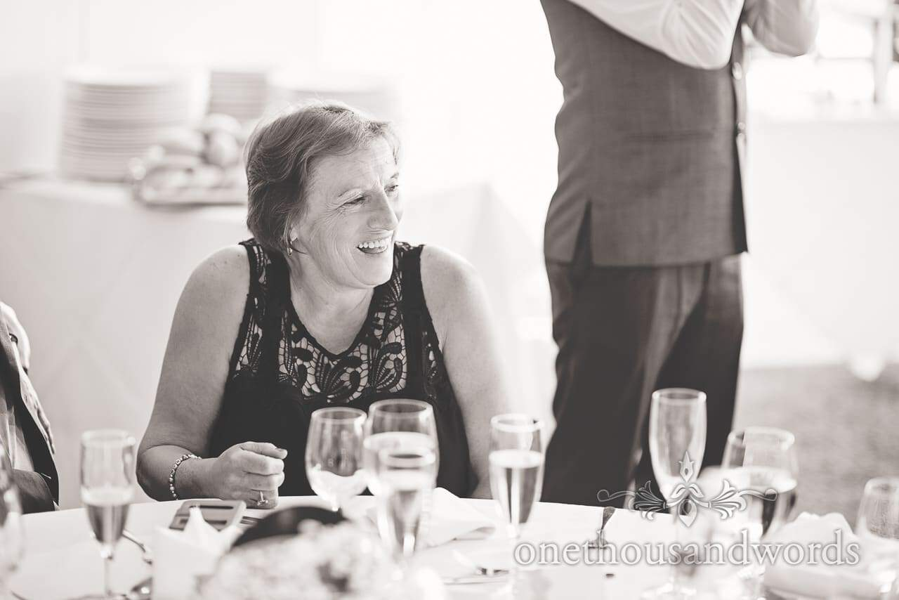 Black and white wedding photograph of guest laughing at wedding speeches