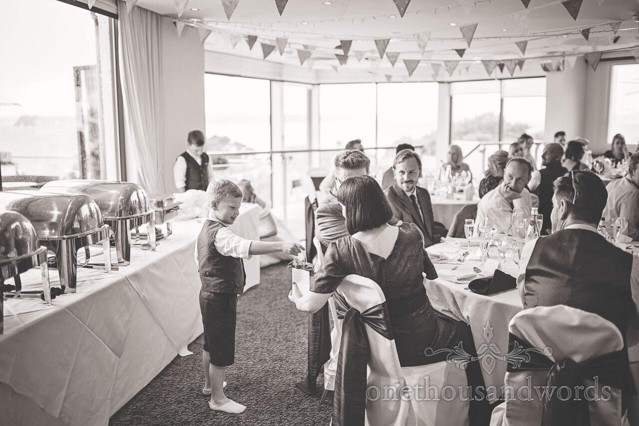 Black and white wedding photograph of page boy giving out presents at wedding