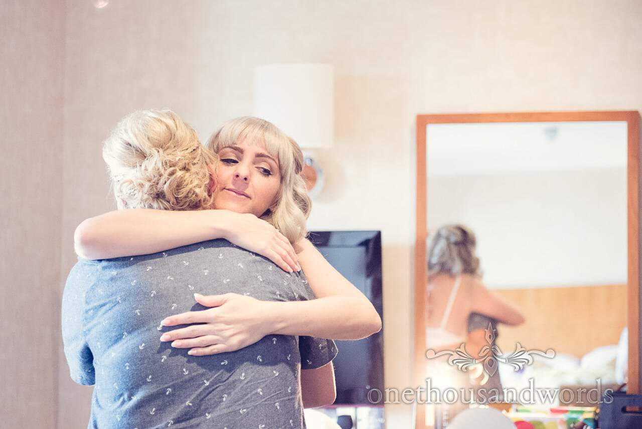 Blonde bride hugs bridesmaid on wedding morning at Harbour Heights Hotel
