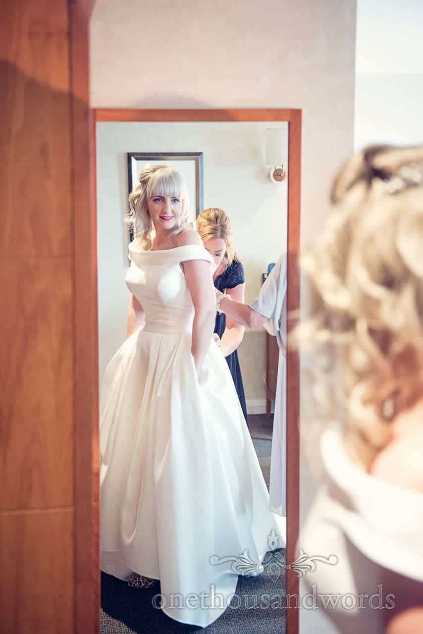 Blonde bride is buttoned into her retro 1950's style wedding dress