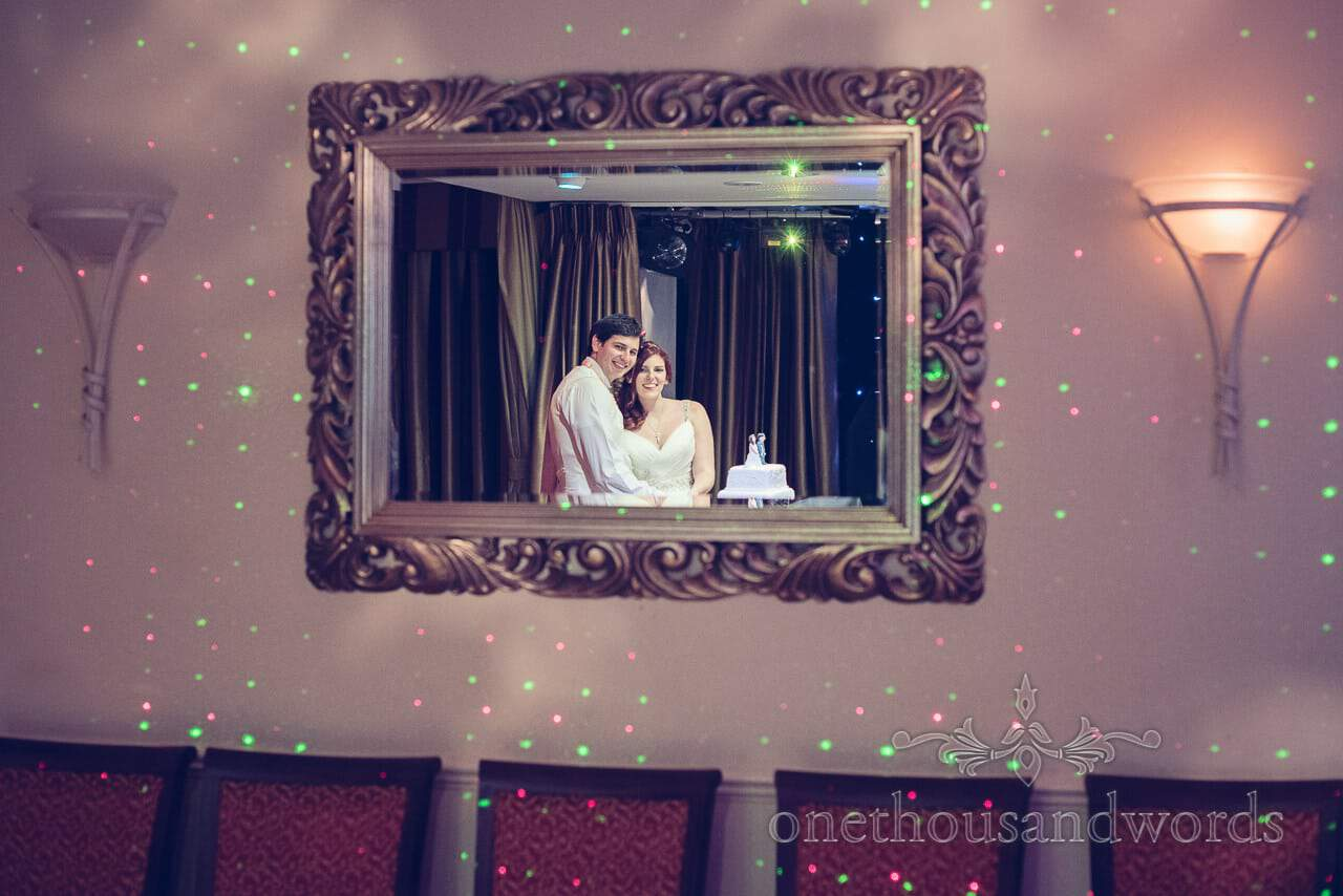 Bride and groom cut the cake reflected in mirror at Bournemouth Hotel Wedding