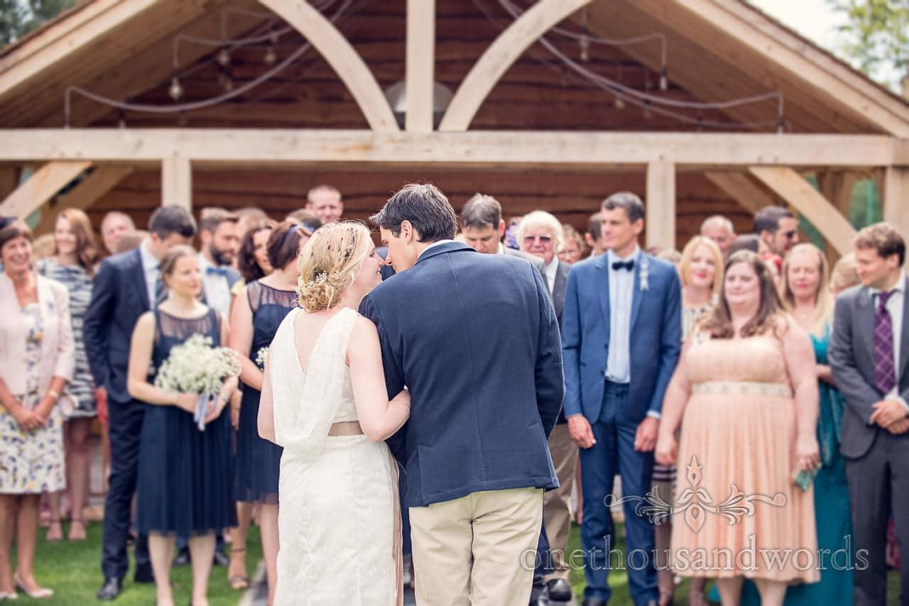 Bride and groom kiss during group photographs at Balmer Lawn Hotel Wedding