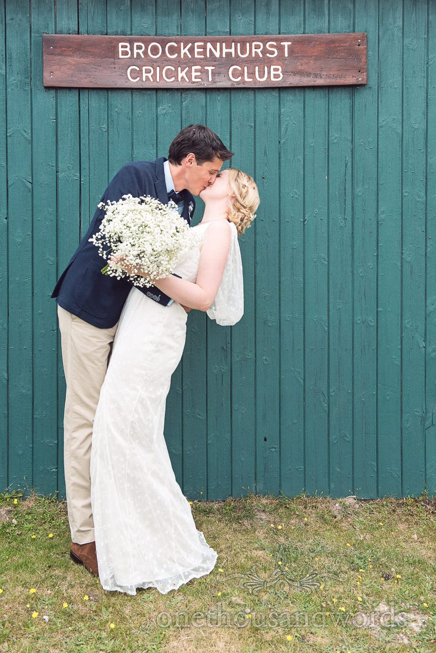 Bride and groom kiss in front of Brockenhurst Cricket Club house